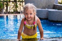 Niña en un traje de baño amarillo en una piscina azul como una sirena niños concepto, moda de los niños imagen de archivo libre de regalías