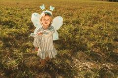 Niña en un traje de la mariposa con las alas en el campo imagenes de archivo