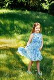 Niña en un vestido azul con un bolso azul en jardín del verano Fotos de archivo libres de regalías