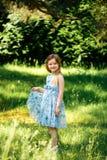 Niña en un vestido azul a disposición en jardín del verano Foto de archivo