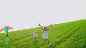 Niña en un vestido que corre a través de campo de trigo verde con la cometa a disposición Niño, niño que corre en jardín y risa almacen de metraje de vídeo