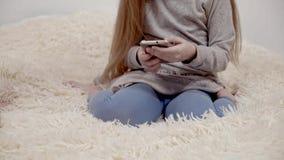 Niña en un vestido que practica surf en Internet con el smartphone que se sienta en cama almacen de metraje de vídeo
