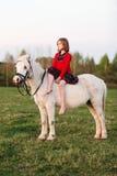 Niña en un vestido que se sienta en un caballo blanco y miradas en la distancia Fotografía de archivo