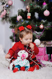 Niña en un vestido rojo en el fondo del árbol de navidad imagen de archivo