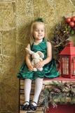 Niña en un vestido verde con una liebre del juguete Imágenes de archivo libres de regalías