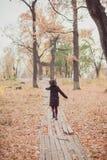 Niña en una capa que funciona con lejos el camino en el parque del otoño imagen de archivo