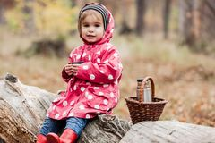 Niña en una chaqueta de guisante que se sienta en un árbol y un té de consumición imagen de archivo libre de regalías
