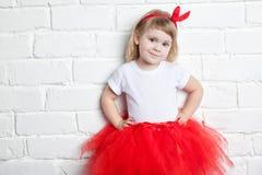 Niña en una falda roja cerca de una pared de ladrillo blanca Fotos de archivo libres de regalías