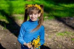 Niña en una hierba verde en una guirnalda de flores en primavera Fotos de archivo libres de regalías