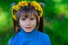 Niña en una hierba verde en una guirnalda de flores en primavera Fotografía de archivo