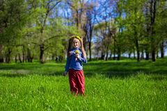 Niña en una hierba verde en una guirnalda de flores en primavera Foto de archivo