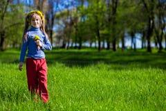 Niña en una hierba verde en una guirnalda de flores en primavera imagenes de archivo