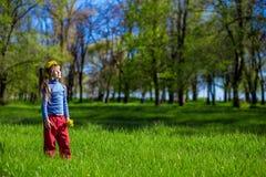 Niña en una hierba verde en una guirnalda de flores en primavera Imagen de archivo