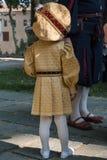 Niña en uniforme de oro con el sombrero grande durante desfile Fotografía de archivo