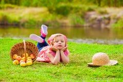 Niña en vaqueros y una camisa cerca de un río con las manzanas Foto de archivo libre de regalías