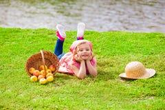 Niña en vaqueros y una camisa cerca de un río con las manzanas Foto de archivo