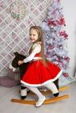 Niña en vestido de la Navidad en caballo del juguete Foto de archivo