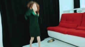 Niña en vestido verde y sus los zapatos del ` s de la madre, bailando almacen de video
