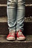 Niña en zapatillas de deporte rojas y vaqueros que se colocan en las escaleras Foto de archivo libre de regalías