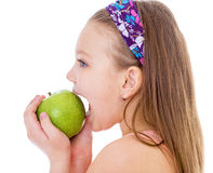 Niña encantadora con la manzana verde. Imagen de archivo