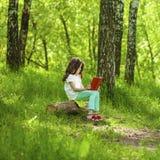 Niña encantadora en bosque con el libro que se sienta en tocón de árbol Fotografía de archivo libre de regalías