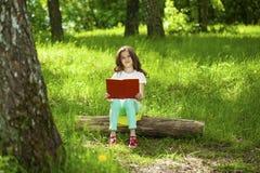 Niña encantadora en bosque con el libro que se sienta en tocón de árbol Fotos de archivo libres de regalías
