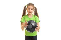 Niña encantadora en camisa verde con el balón de fútbol en manos Imagenes de archivo