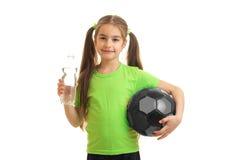 Niña encantadora en uniforme del verde con el balón de fútbol Foto de archivo