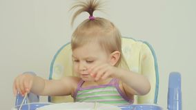 Niña encantadora que come los espaguetis con sus fingeres y que goza de ellos almacen de video