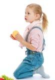 Niña encantadora que se arrodilla sosteniendo una manzana Fotografía de archivo