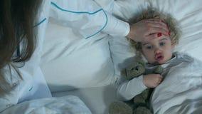 Niña enferma con el juguete amado que miente mientras que doctor de la enfermera que toma temperatura almacen de metraje de vídeo