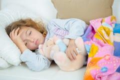 Niña enferma en el sofá con fiebre Imágenes de archivo libres de regalías