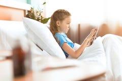 Niña enferma que usa la tableta digital en cama de hospital Fotografía de archivo