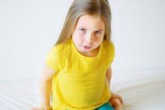 Niña enojada con la camiseta amarilla sobre el fondo blanco Fotos de archivo libres de regalías