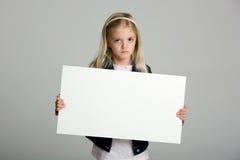 Niña enojada que lleva a cabo una muestra en blanco Fotos de archivo libres de regalías