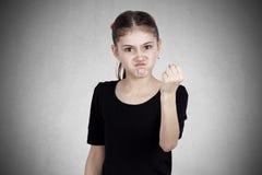 Niña enojada que muestra el puño alguien Imagen de archivo