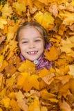 Niña enterrada en amarillo de las hojas de otoño Foto de archivo libre de regalías