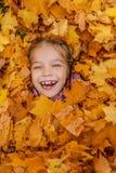 Niña enterrada en amarillo de las hojas de otoño Fotografía de archivo