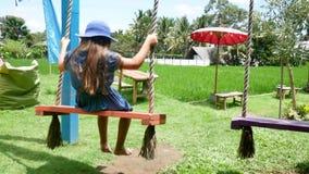 Niña europea que juega el oscilación de madera con felicidad Asia, Bali indonesia almacen de metraje de vídeo