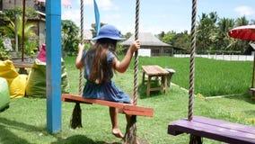 Niña europea que juega el oscilación de madera con felicidad Asia, Bali indonesia metrajes