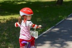 Niña expresiva con el casco de seguridad rojo colorido que monta una bicicleta Imagenes de archivo