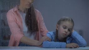 Niña favorable de la madre detrás de la ventana lluviosa, sufrimiento del niño de tiranizar almacen de metraje de vídeo