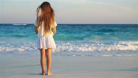 Niña feliz adorable en la playa blanca que mira en el océano Mar ruidoso y un pequeño niño lindo metrajes