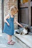 Niña feliz adorable y un gato Imagenes de archivo