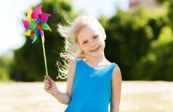Niña feliz con el molinillo de viento colorido en el verano Imágenes de archivo libres de regalías