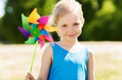 Niña feliz con el molinillo de viento colorido en el verano Fotografía de archivo libre de regalías
