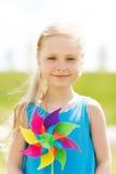 Niña feliz con el molinillo de viento colorido en el verano Imagen de archivo libre de regalías