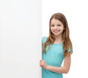 Niña feliz con el tablero blanco en blanco Foto de archivo