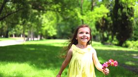 Niña feliz con el vestido amarillo que corre descalzo en hierba verde en el parque almacen de metraje de vídeo