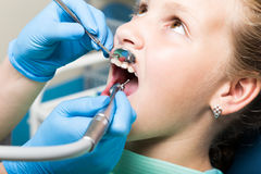 Niña feliz con la boca abierta que experimenta el tratamiento dental en la clínica Dentista comprobado y que cura los dientes un  Foto de archivo libre de regalías